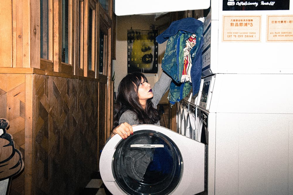 a girl putting her clothes in a laundry machine