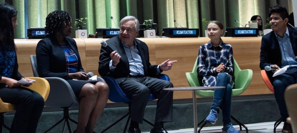 UN Secretary-General, Antonio Guterres, Greta Thunberg, and three others sitting on chairs