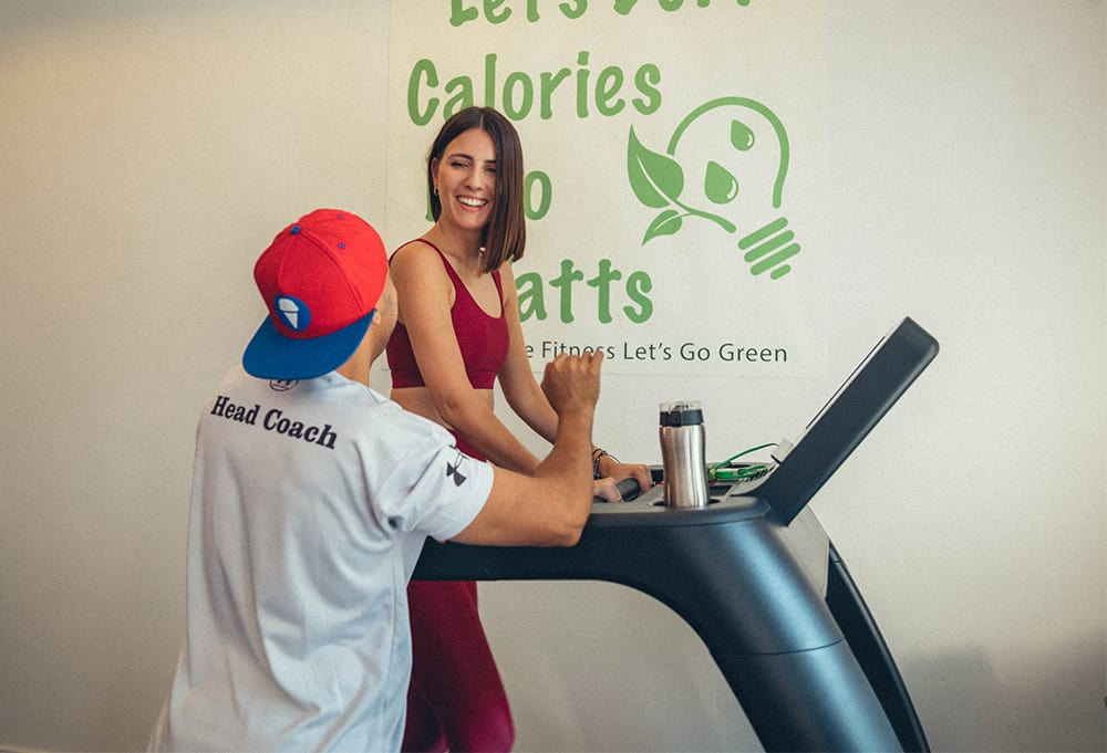 A girl and a coach on a treadmill at eco-friendly gym in Singapore