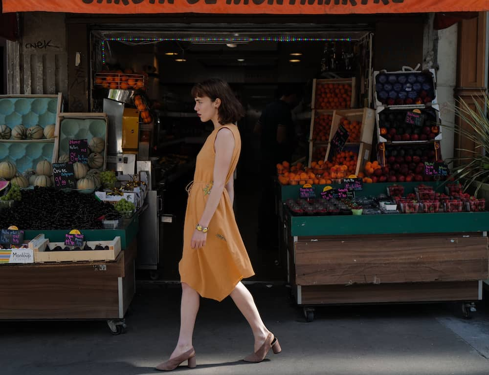 Girl walking in front of vegetables